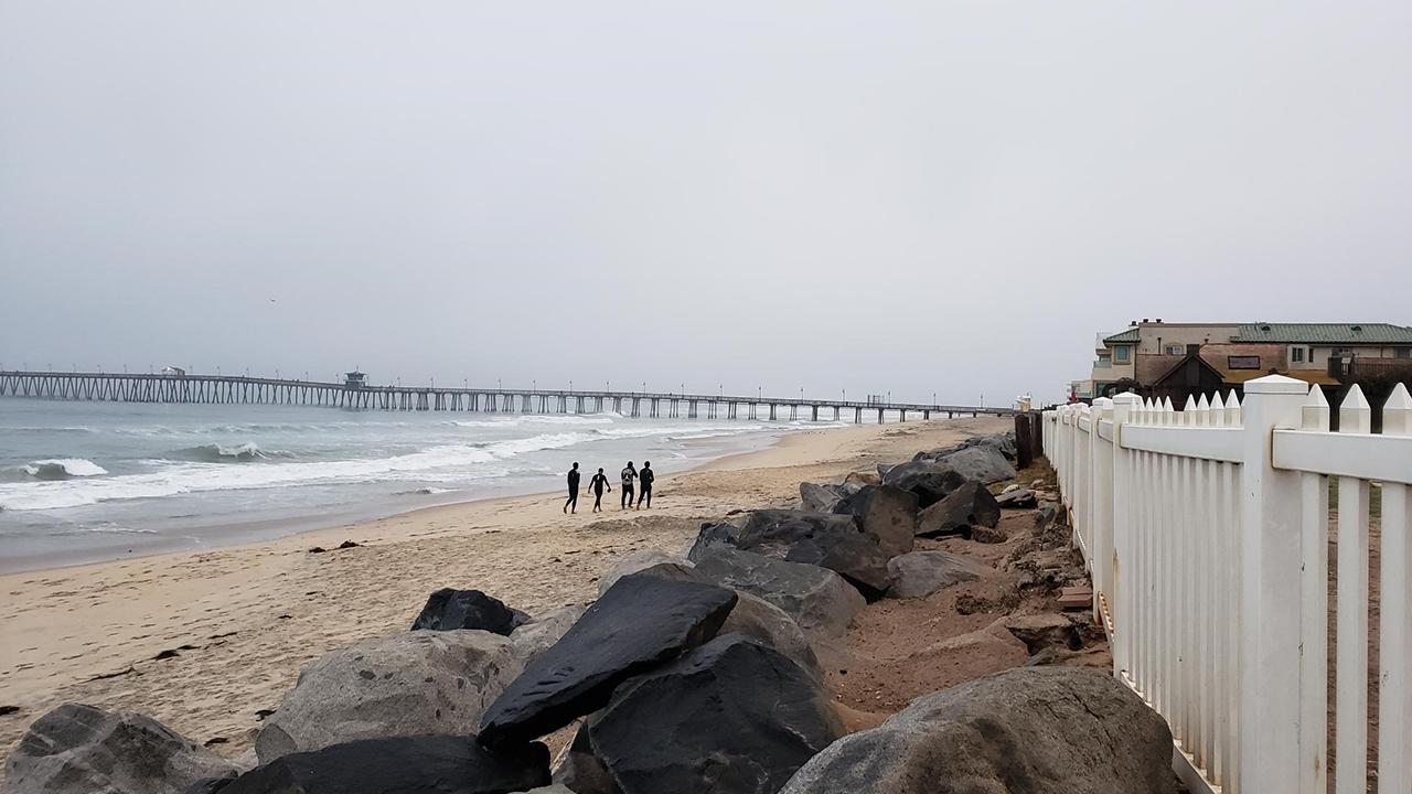 Four Men Swim Around Border Wall